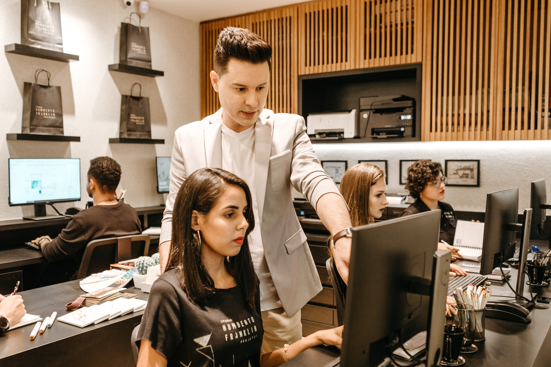man-teaching-woman-in-front-of-monitor-3285203